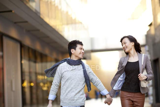 Couple chinois marchant dans la rue et se tenant la main — Photo de stock