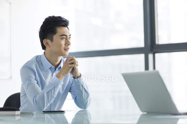 Китайський бізнесмен, сидячи руками, склала в офісі — стокове фото