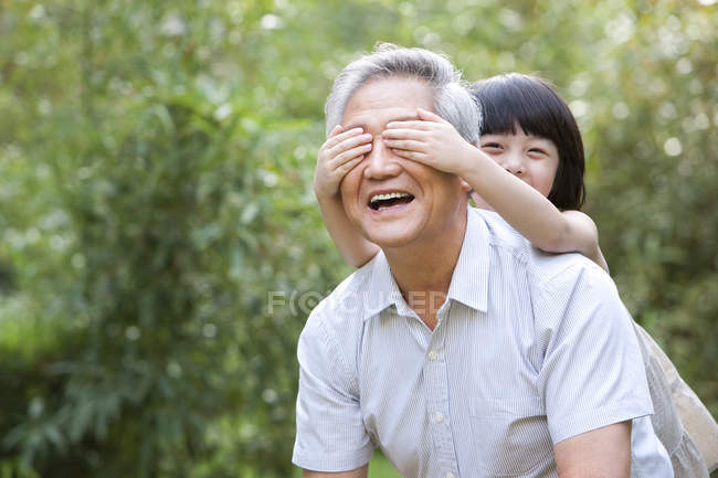 Chinese girl covering grandfather eyes with hands in garden — Stock Photo