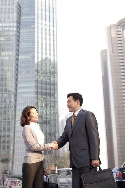 Китайський ділові люди вітають один одного у фінансовому районі — стокове фото