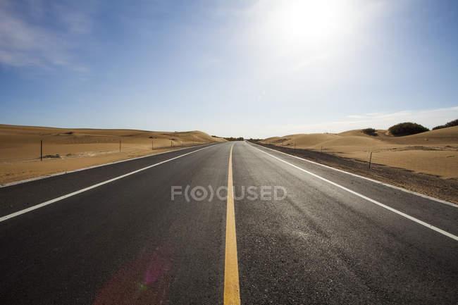 Straße, die durch die Wüste in der chinesischen Provinz Innere Mongolei — Stockfoto