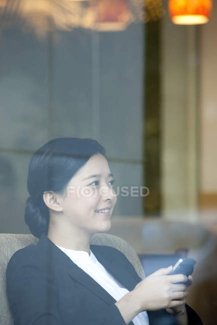 Chinese businesswoman sitting with smartphone in cafe — Stock Photo