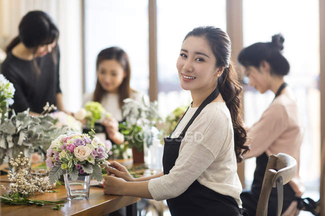 Young Chinese women learning flower arrangement with art teacher — Stock Photo