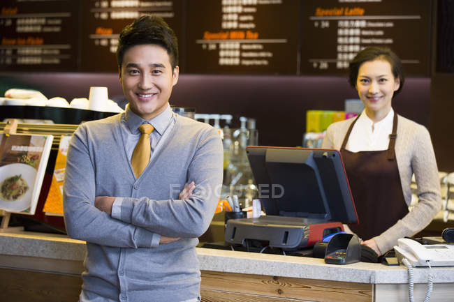 Portrait of Chinese coffee store shopkeeper and waitress at counter — Stock Photo