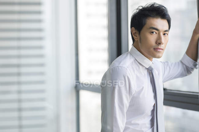 Chinese businessman standing by window and looking in camera — Stock Photo