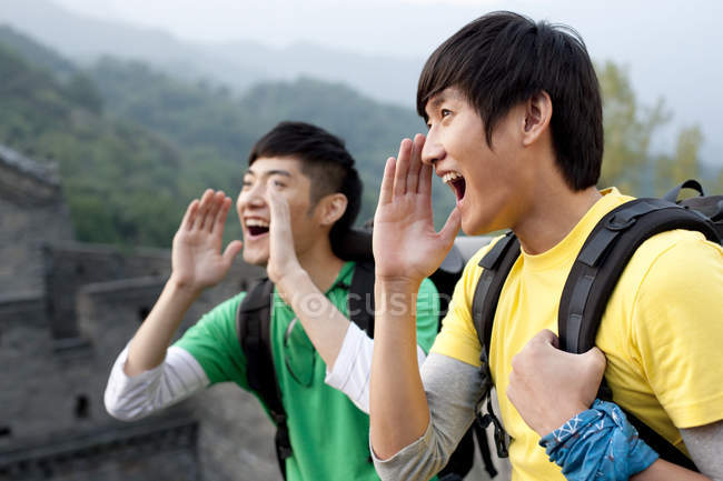 Chinese male friends shouting on Great Wall — Stock Photo