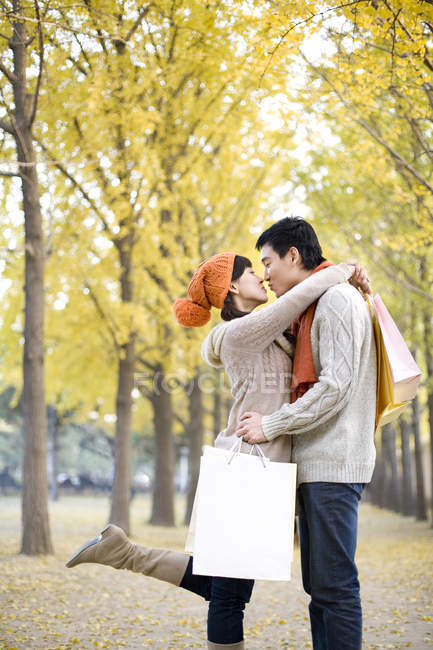 Chinese couple with shopping bags embracing and kissing in park — Stock Photo