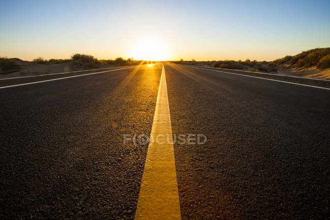 Road going through wilderness area on sunset in Inner Mongolia province, China — Stock Photo