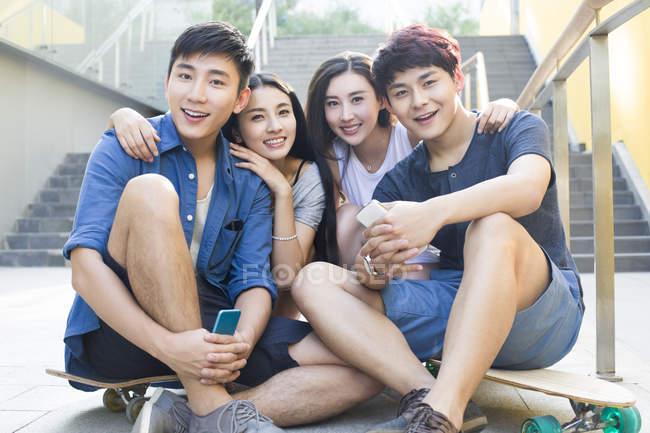 Китайские друзья, сидя с смартфонов и скейтбордах на улице — стоковое фото