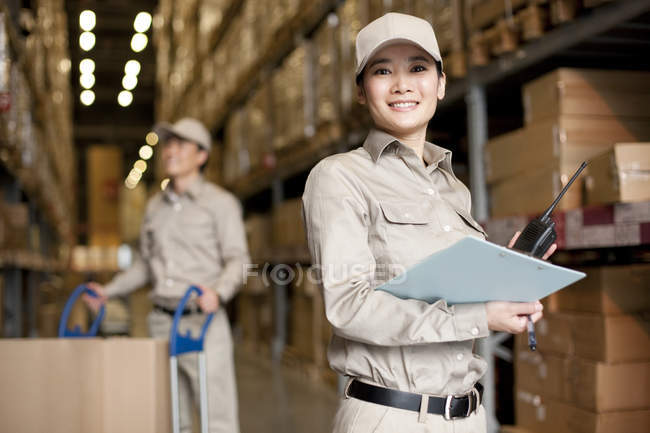 Male and female Chinese workers with walkie-talkie and clipboard — Stock Photo