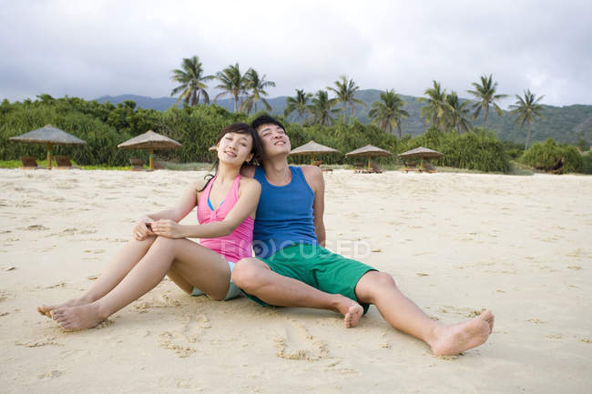 Young Chinese couple sitting at Hainan beach — Stock Photo