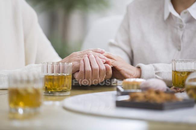 Abgeschnittene Ansicht von älteren Frauen, die sich beim Teetrinken an den Händen halten — Stockfoto