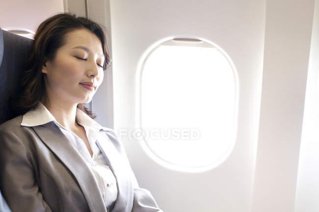 Chinese businesswoman resting on seat on flight — Stock Photo