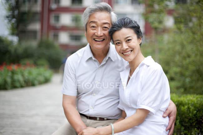 Старшая китайская пара сидит в парке и держит за руки — стоковое фото