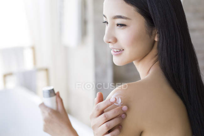 Chinese woman applying moisturizer to shoulder — Stock Photo