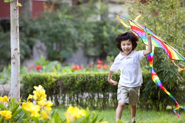 Petit garçon chinois volant cerf-volant dans le jardin — Photo de stock