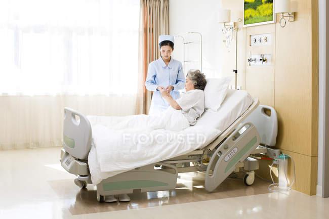 Китайские медсестры, позаботиться о старшие женщины в больнице — стоковое фото