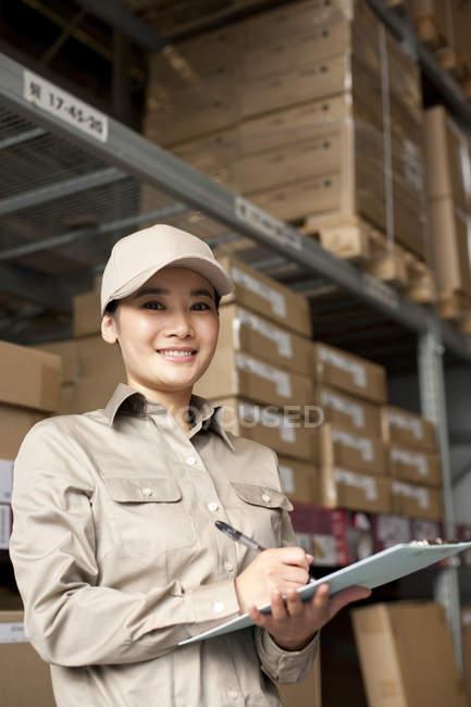 Trabajador almacén chino femenino con portapapeles - foto de stock