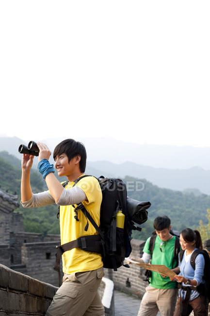 Китаєць з біноклі, дивлячись на вигляд з друзями на Велика Стіна — стокове фото