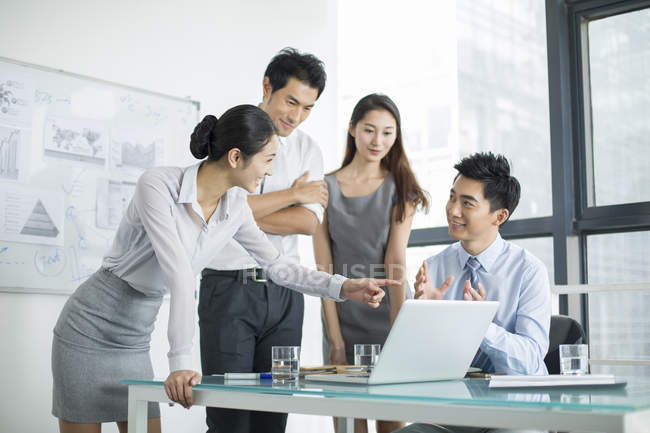 Chinese business team talking in meeting and pointing at laptop — Stock Photo