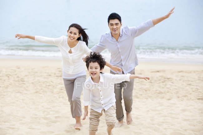 Китайський батьків з сином працює з обіймами розкритими на піщаний пляж — стокове фото