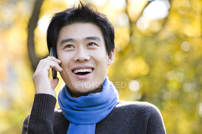 Young Chinese man talking on phone in park — Stock Photo