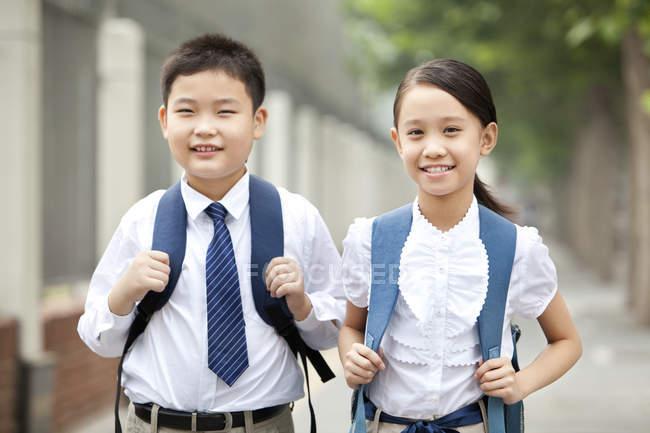 Joyeux camarades de classe en uniforme scolaire, posant sur la rue — Photo de stock