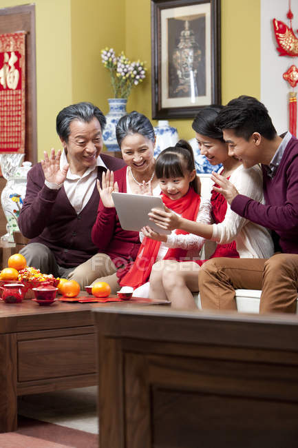 Family using digital tablet for video chatting on Chinese New Year — Stock Photo