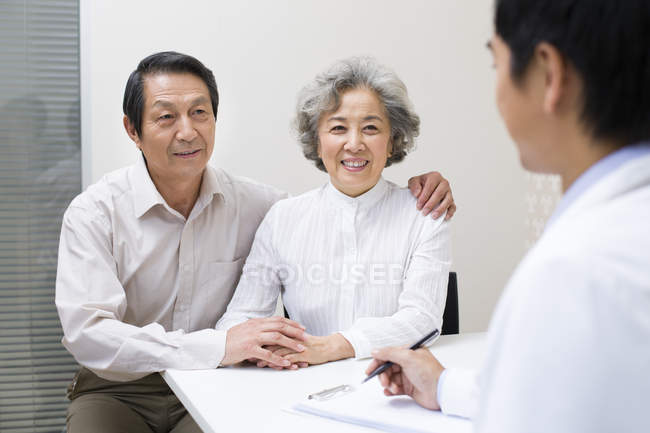 Chinese senior couple with doctor in hospital — Stock Photo