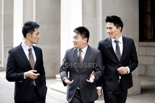 Chinese businessmen walking and talking on street — Stock Photo