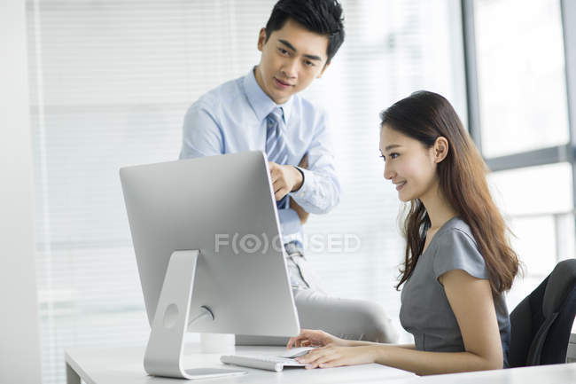Chinese businesswoman and businessman using computer in office — Stock Photo