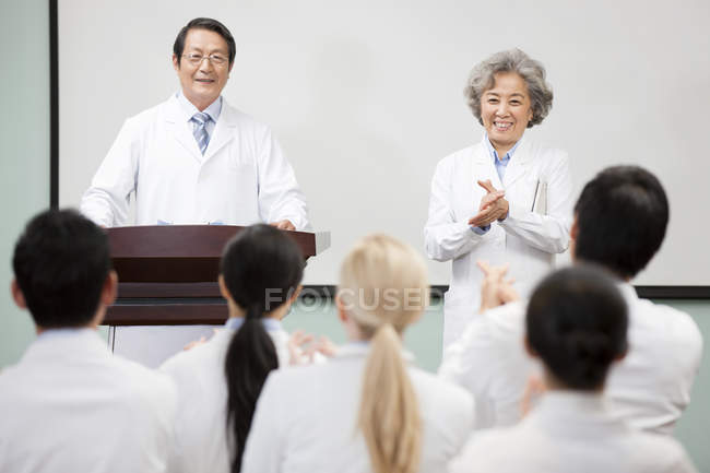 Chinese medical workers clapping on seminar — Stock Photo