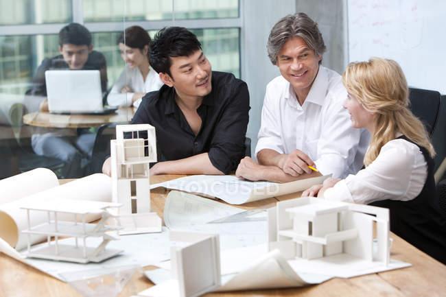 Equipo de arquitectos discutiendo planos - foto de stock