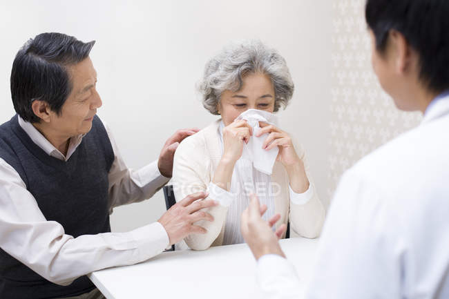 Chinese senior man consoling woman in hospital — Stock Photo