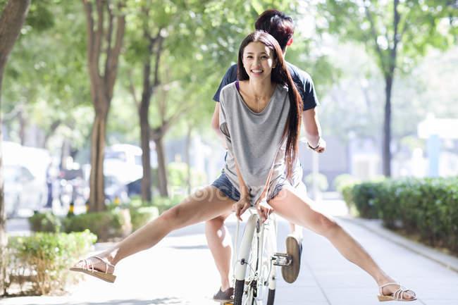 Китаянка на велосипеде с мужчиной — стоковое фото