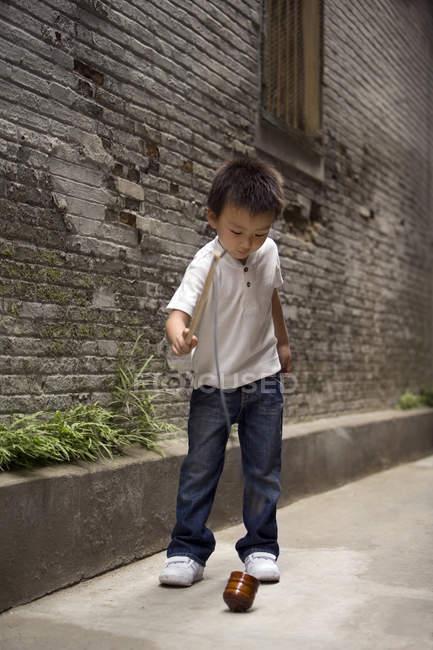 Chinois garçon jouer avec toupie dans ruelle — Photo de stock