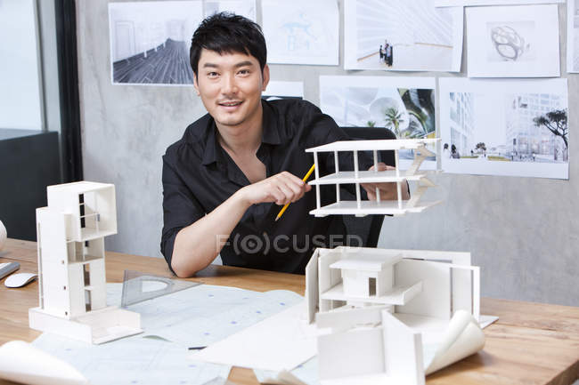 Chinese architect sitting with architectural model — Stock Photo