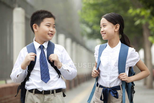 Cheerful classmates in school uniform posing on street — Stock Photo