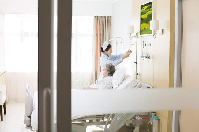 Chinoise infirmière aidant patient changeant saline goutte à goutte — Photo de stock