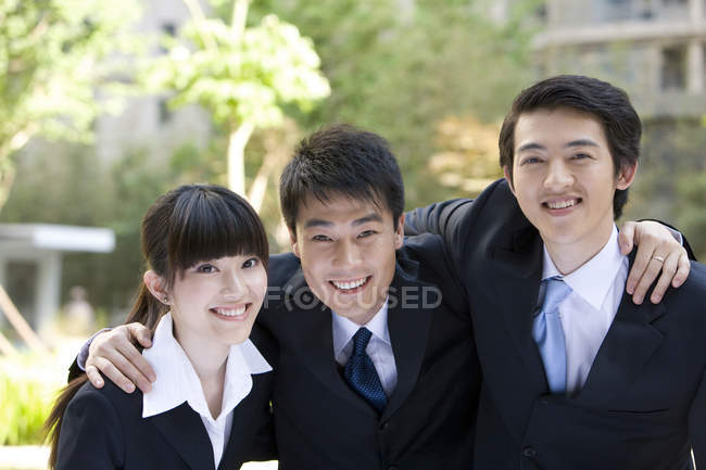 Chinese business professionals embracing and looking in camera on street — Stock Photo