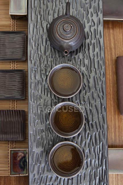 Tasses de thé et théière chinoise dans une rangée, vue de dessus — Photo de stock