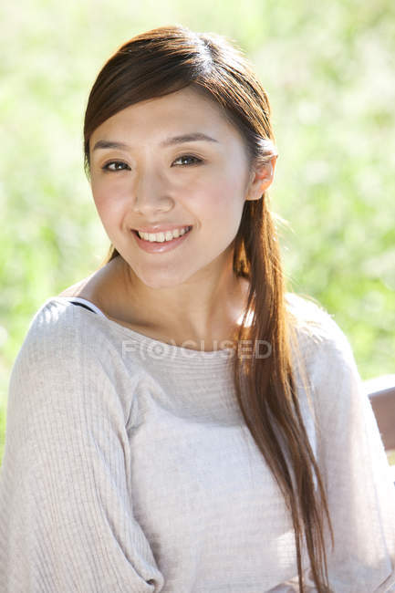 Portrait of Chinese woman in sunny park — Stock Photo