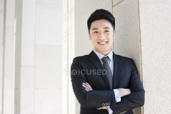 Chinese businessman standing with arms crossed — Stock Photo