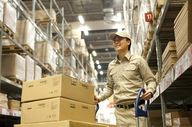 Chinesischer Lagerarbeiter schiebt Kisten — Stockfoto