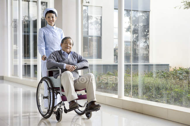 Enfermeira chinesa empurrando homem sênior em cadeira de rodas — Fotografia de Stock