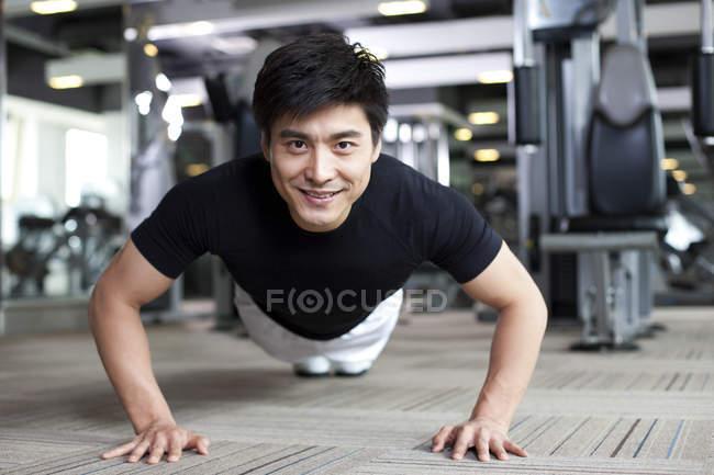 Chinesischer Mann tun Push ups in Turnhalle — Stockfoto