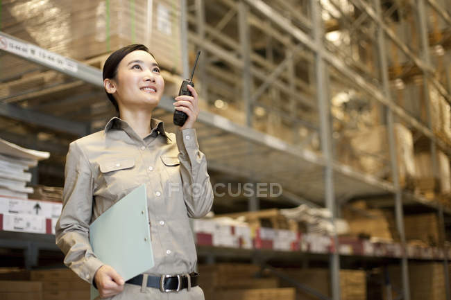 Female Chinese warehouse worker using walkie-talkie with clipboard — Stock Photo