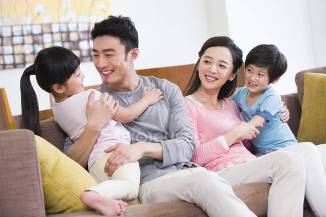 Китайські родини з двома дітьми, відпочиваючи в диван — стокове фото