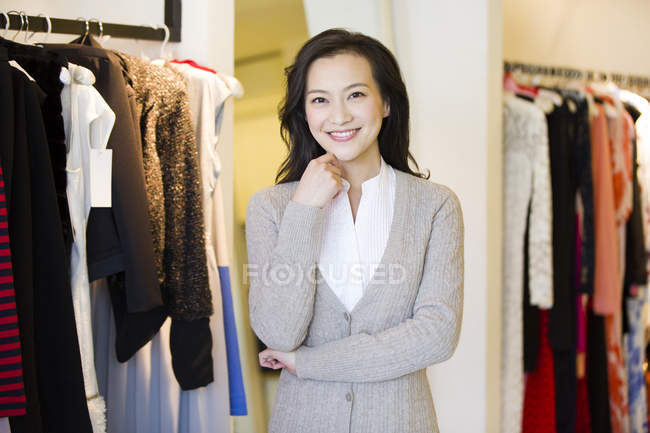 Chinese woman standing  in clothing store and looking in camera — Stock Photo