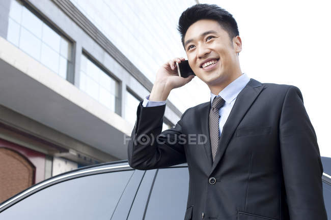 Китайский бизнесмен разговаривает по телефону перед машиной — стоковое фото